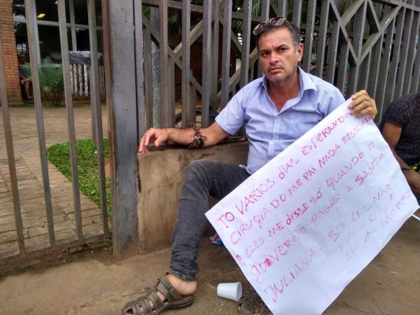 Homem se acorrenta na frente de hospital para cobrar cateterismo no pai internado há 10 dias no AC