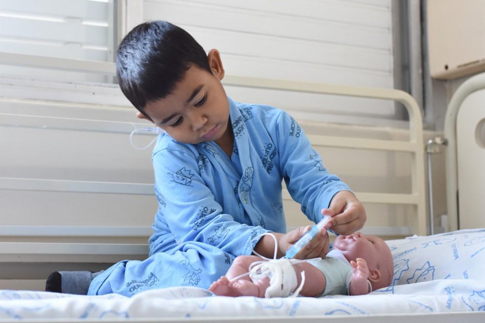 Injeções fazem parte da rotina de Artur - e consequentemente, de seu boneco — Foto: Camila Mendes/Divulgação Hospital Pequeno Príncip