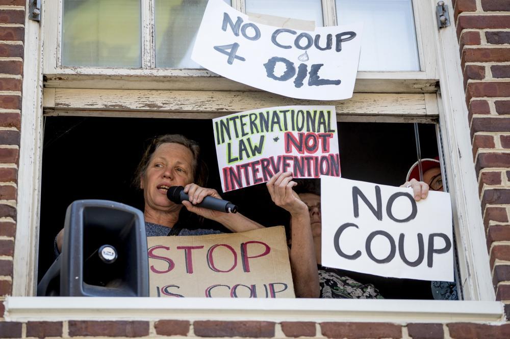 Manifestantes contrários a Juan Guaidó ocupam embaixada da Venezuela em Washington: 'Não ao golpe pelo petróleo', diz um dos cartazes — Foto: Andrew Harnik/AP Photo