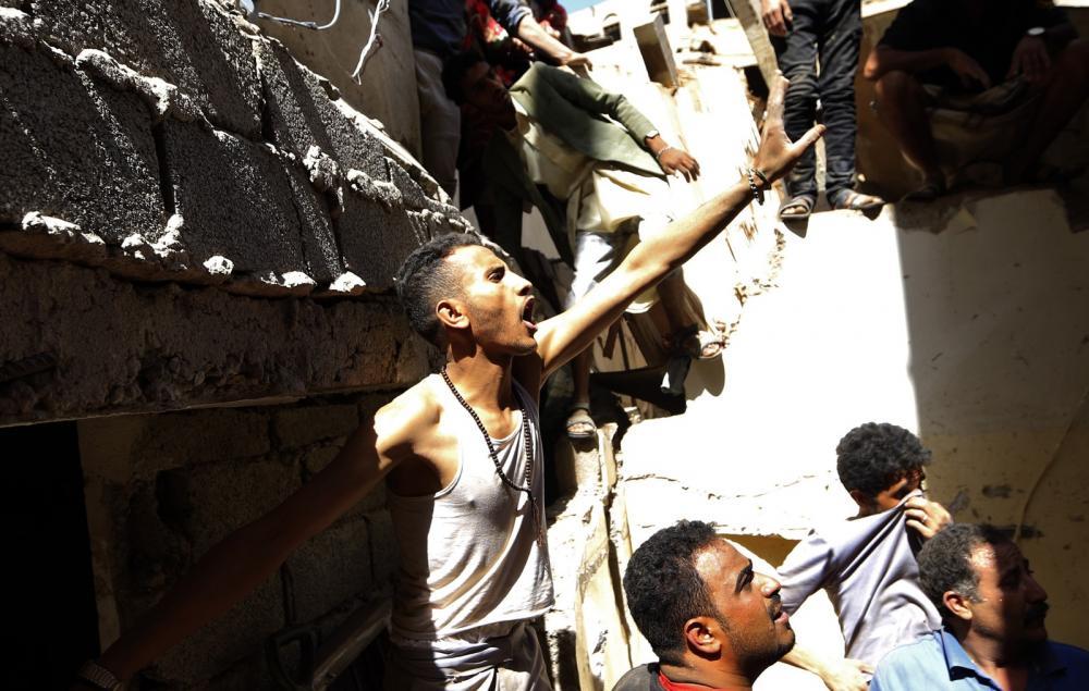 Iemenitas se protegem de poeira depois de bombardeios liderados pelos sauditas, na capital Sanaa, na quinta (16) — Foto: Mohammed HUWAIS/AFP