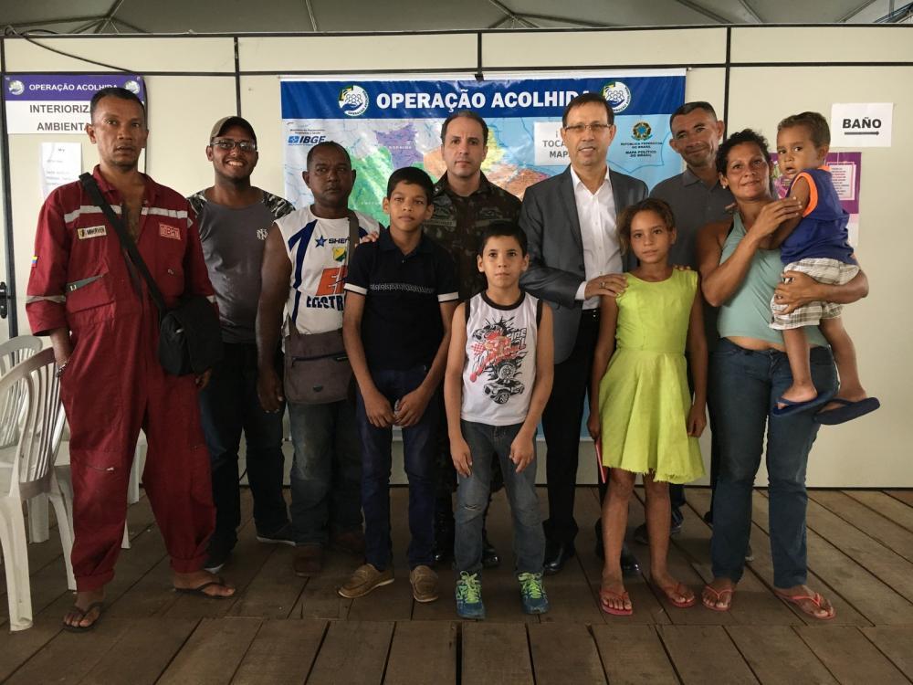 Bilionário Carlos Wizard (ao centro) acolhe venezuelanos recém-chegados ao Brasil — Foto: Emily Costa/G1 RR