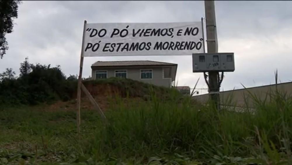 'Do pó viemos, no pó estamos morrendo', protestam moradores de Contenda, em faixa instalada para pedir asfalto — Foto: Reprodução/RPC