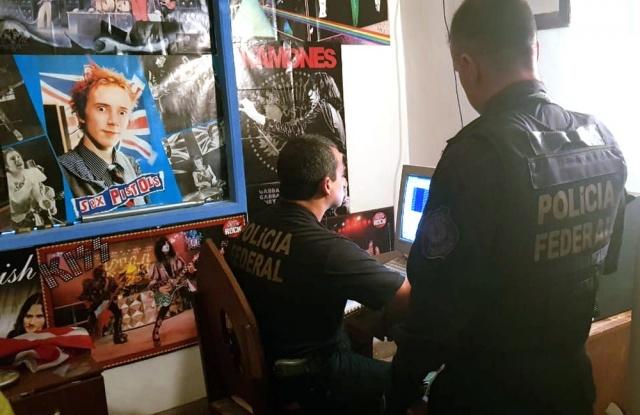 Policiais federais analisam o computador de um dos presos — Foto: Polícia Federal