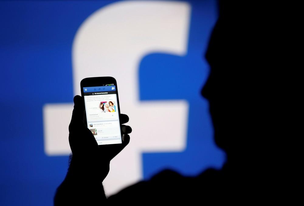 Homem usa aplicativo do Facebook no celular. — Foto: Dado Ruvic/Reuters