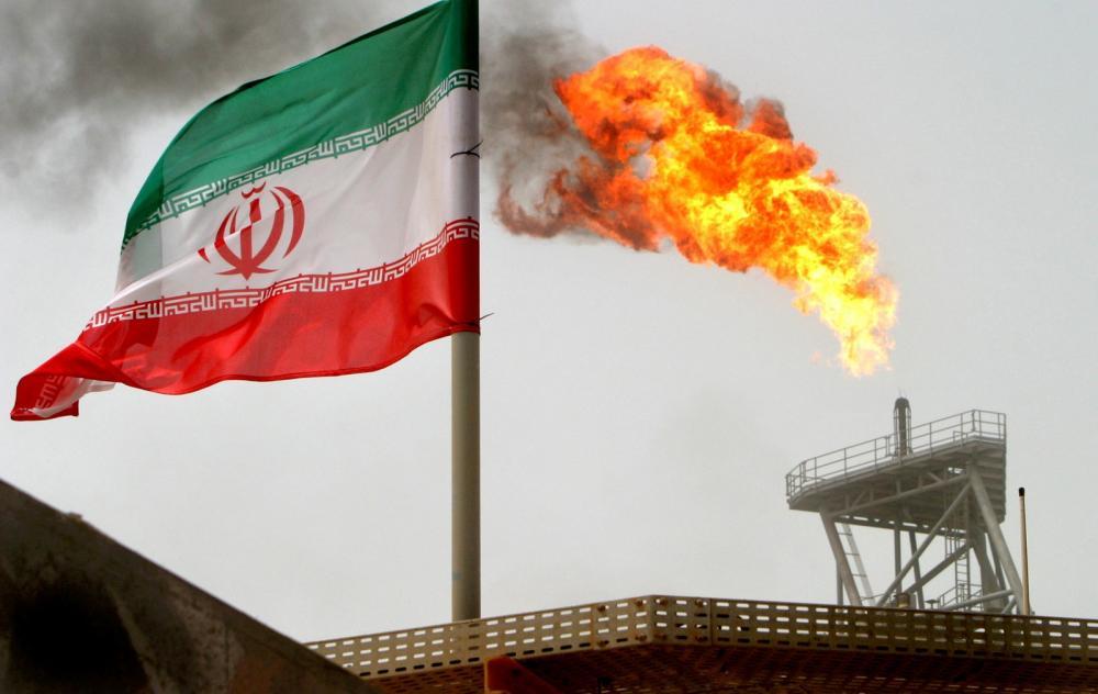 Uma tocha de gás em uma plataforma de produção de petróleo ao lado de uma bandeira iraniana no Golfo Pérsico, no Irã. — Foto: Raheb Homavandi/File Photo/Reuters
