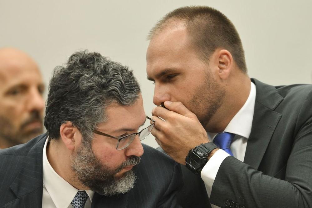 O deputado Eduardo Bolsonaro (PSL-SP) fala ao ouvido do ministro Ernesto Araújo durante audiência pública, em março deste ano, na comissão de Relações Exteriores da Câmara dos Deputados — Foto: Marcelo Camargo/Agência Brasil